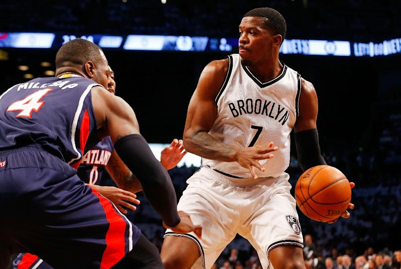 Joe Johnson of the Brooklyn Nets looks to make a play as he is defended by Paul Millsap and Jeff Teague of the Atlanta Hawks during game six in the first round of the 2015 NBA Playoffs at Barclays Center on May 1, 2015 in New York City