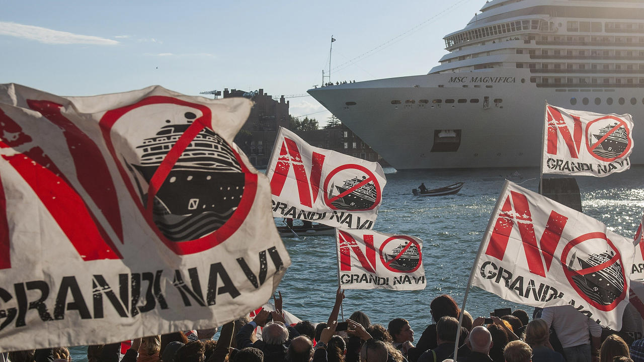 "Protesters wave ""No Big Ships"" flags during the the passage of a cruise ship on October 4, 2015 in Venice, Italy."