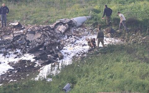 Israeli security forces walk next to the remains of an F-16 Israeli war plane near the Israeli village of Harduf - Credit: Reuters
