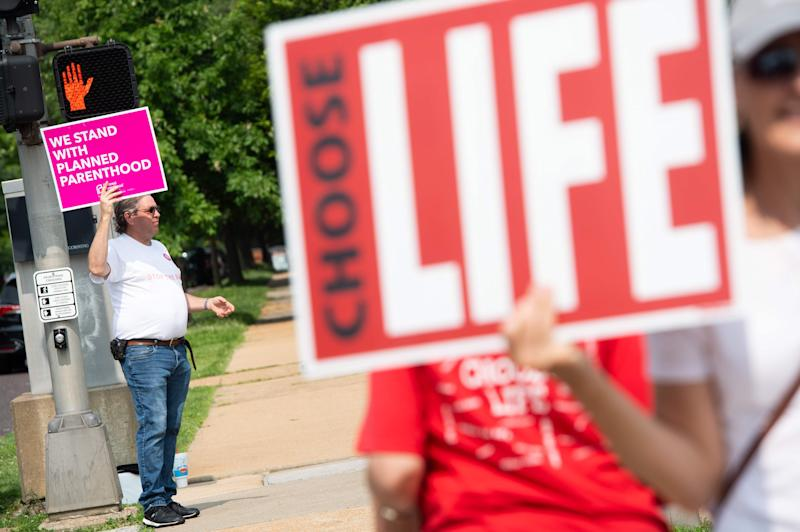 A supporter of Planned Parenthood stands near an anti-abortion demonstrators as they hold a protest outside the Planned Parenthood Reproductive Health Services Center in St. Louis, Missouri, May 31, 2019, the last location in the state performing abortions. - Missouri was set Friday to become the first US state in half a century without abortion services unless a court steps in at the last moment to keep its sole remaining abortion clinic in operation.Unless the courts rule in its favor in an emergency motion, the St Louis clinic will lose at midnight (0400 GMT) its license to perform the procedure. (Photo by SAUL LOEB / AFP)SAUL LOEB/AFP/Getty Images ORIG FILE ID: AFP_1H41IQ