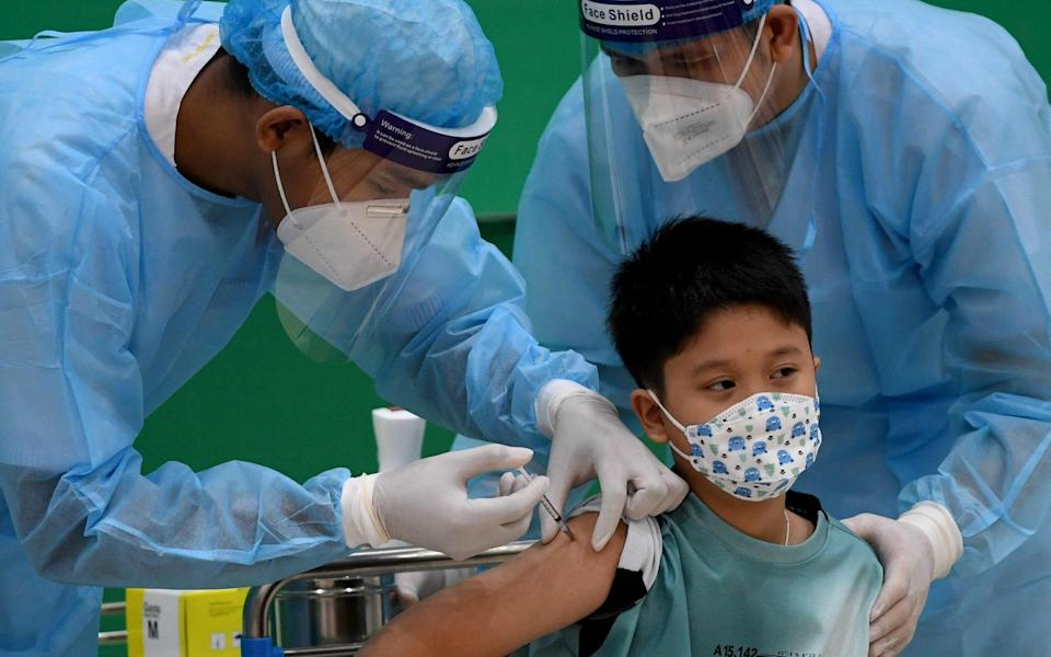 The grandson of Cambodia's Prime Minister Hun Sen receives a dose of the Sinovac Covid-19 coronavirus vaccine at the Peace Palace in Phnom Penh on September 17 - TANG CHHIN SOTHY/AFP