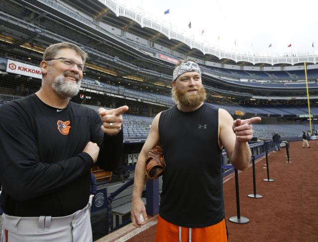 Baltimore Orioles pitching coach Doug Brocail, left, and Baltimore Orioles starting pitcher Andrew Cashner gesture as they talk to a group of visiting students on the field before a baseball game between the New York Yankees and the Baltimore Orioles, Tuesday, May 14, 2019, in New York. The game was postponed due to inclement weather so th pair were heading back to the clubhouse after Cashner worked out. (AP Photo/Kathy Willens)