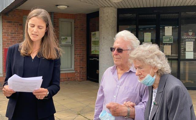 Alice Hardy, of Hodge Jones & Allen Solicitors, reads a statement on behalf of Susan Nicholson's parents Peter and Elizabeth Skelton while standing next to them outside the inquest in Crawley