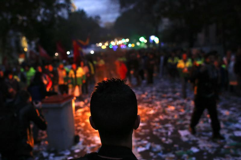 A man looks at a fire during a protest in Madrid
