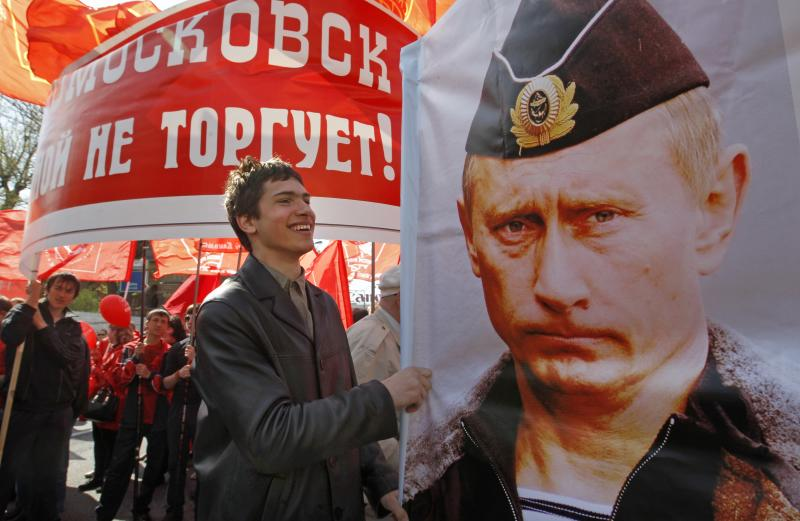 A Communist Party supporter holds a poster depicting Russia's Prime Minister Vladimir Putin during a communist Party supporters rally to mark May Day in Moscow, Russia, Tuesday, May 1, 2012. (AP Photo/Mikhail Metzel)
