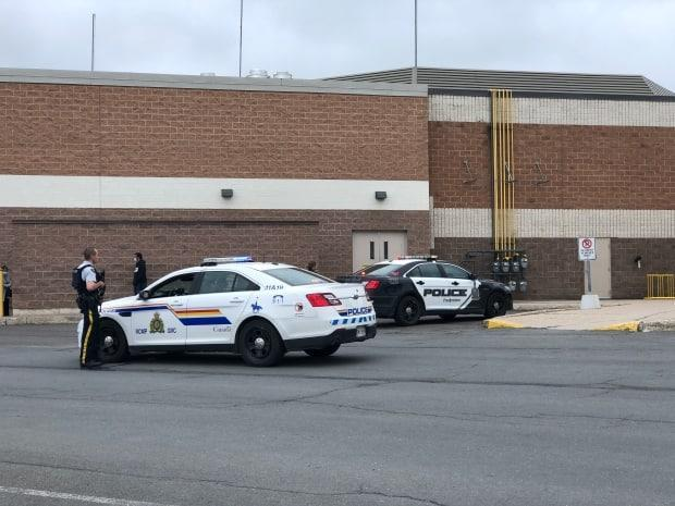 Police armed with long guns are shown outside an entrance to the Regent Mall in Fredericton on Saturday. (Gary Moore/CBC - image credit)