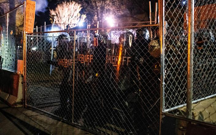 Law enforcement officers push up to the gate outside the police headquarters in Brooklyn Center-Stephen Maturen & # xa0; / Getty
