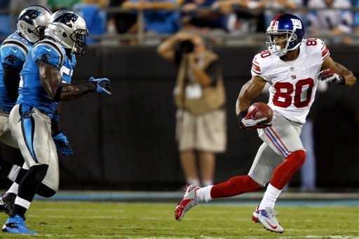 New York Giants wide receiver Victor Cruz (80) runs after a catch as Carolina Panthers linebackers Jon Beason (52) and James Anderson (50) defend during the second quarter of an NFL football game in Charlotte, N.C., Thursday, Sept. 20, 2012. (AP Photo/Bob Leverone)