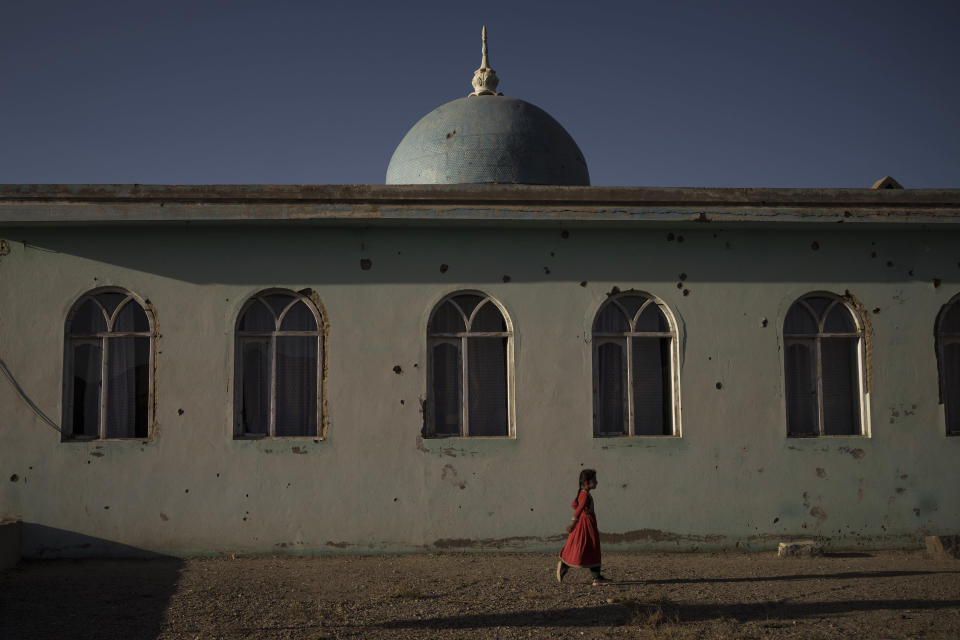An Afghan girl walks outside a mosque marked by bullet holes at a village in Wardak province, Afghanistan, Monday, Oct. 11, 2021. (AP Photo/Felipe Dana)