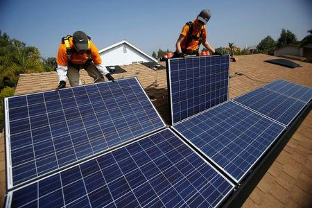 Solar technicians install solar panels on the roof of a house in Mission Viejo