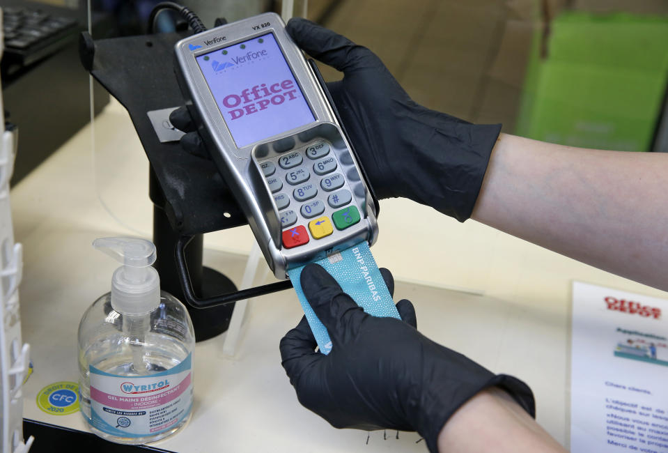 PARIS, FRANCE - APRIL 17: A woman wearing protective gloves  inserts her credit card into a payment terminal during the coronavirus (COVID 19) outbreak on April 17, 2020, in Paris, France. The limit of contactless payment will increase from 30 to 50 euros on May 11, the French Banking Federation said on Thursday due to the Coronavirus epidemic. The Coronavirus (COVID-19) pandemic has spread to many countries across the world, claiming over 146,000 lives and infecting over 2.1 million people. (Photo by Chesnot/Getty Images)