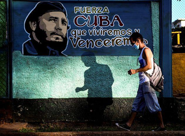 TOPSHOT - A man walks by a mural depicting Cuban late leader Fidel Castro -who would have turned 95 today- in Havana, on August 13, 2021. - Cubans pay tribute to Fidel Castro on the 95th anniversary of his birth, despite the situation the nation is going through due to the presence of COVID-19. (Photo by YAMIL LAGE / AFP) (Photo by YAMIL LAGE/AFP via Getty Images) (Photo: YAMIL LAGE via Getty Images)