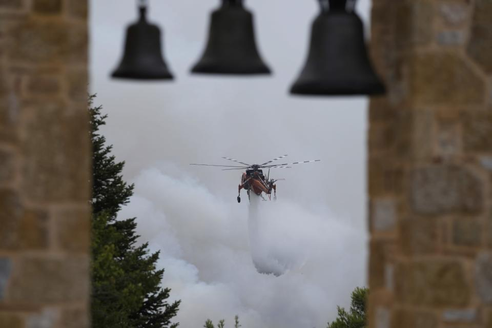 An helicopter drops water over a fire in Ippokratios Politia village, about 35 kilometres (21 miles) north of Athens, Greece, Friday, Aug. 6, 2021. Thousands of residents of the Greek capital have fled to safety from a wildfire that burned for a fourth day north of Athens as crews battle to stop the flames reaching populated areas, electricity installations and historic sites. (AP Photo/Thanassis Stavrakis)