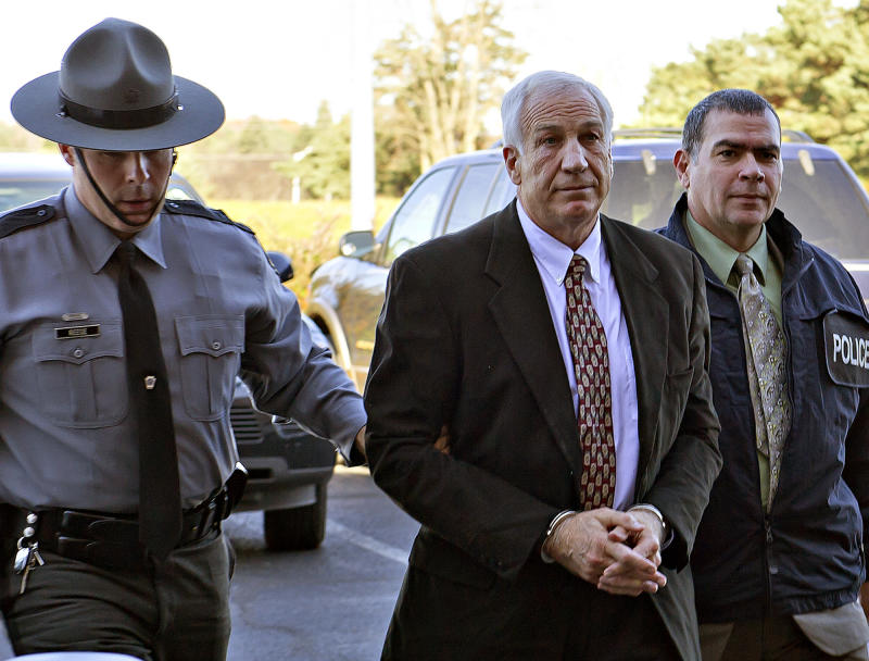 FILE - A Nov. 5, 2011 file photo shows former Penn State football defensive coordinator Jerry Sandusky, center, wearing handcuffs as he is escorted to the office of Centre County Magisterial District Judge Leslie A. Dutchcot, in State College, Pa.  Sandusky is charged with more than 50 counts related to sexual abuse over a 12-year period.  (AP Photo/The Patriot-News, Andy Colwell, File)