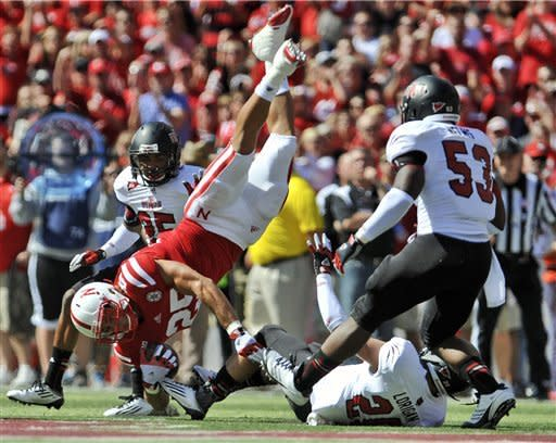 Nebraska's Kyler Reed, top, is upended by Arkansas State's Cole Lorigan (20) as Arkansas State's Nick Nelms (53), right, and Chaz Scales (25), watch during the first half of an NCAA college football game in Lincoln, Neb., Saturday, Sept. 15, 2012. (AP Photo/Dave Weaver)