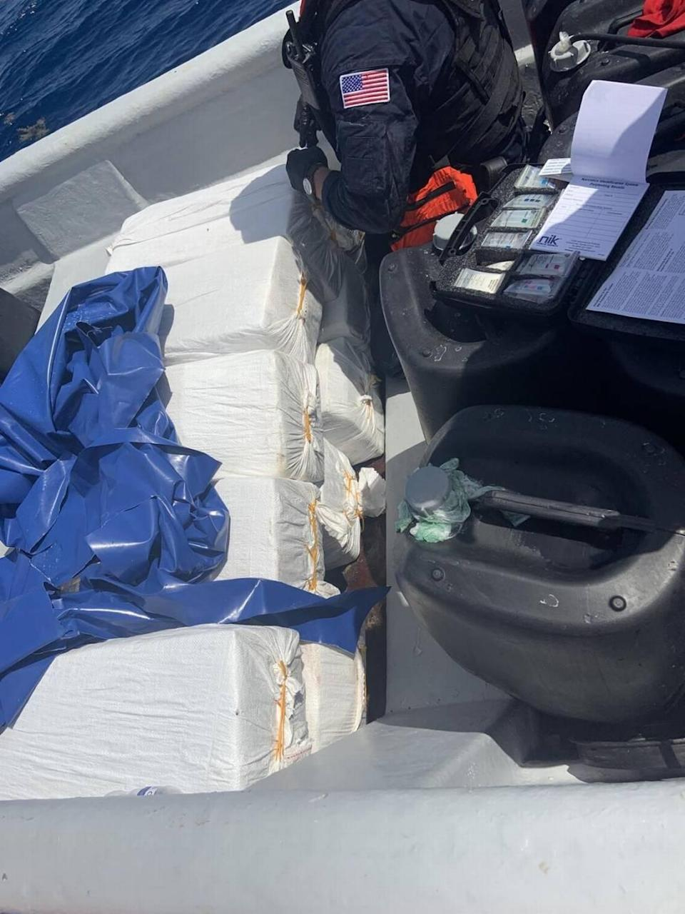 A U.S. Coast Guard crew member stands by a stack of 10 bales of cocaine on board a boat the agency stopped south of the Dominican Republic Wednesday, Sept. 22, 2021.