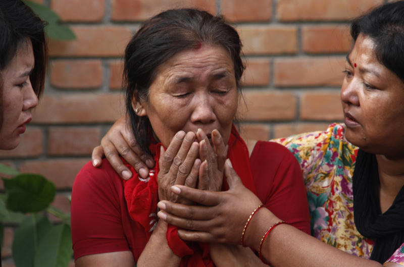 Mother, center, of crew member Asmita Shrestha who died in the plane crash breaks down as she waits to receive her daughter's dead body at the Teaching hospital in Katmandu, Nepal, Sunday, Sept. 25, 2011. A plane that was carrying tourists to view Mount Everest crashed while attempting to land in Nepal on Sunday, killing all 19 people on board, including 13 foreigners, officials said.(AP Photo/Niranjan Shrestha)