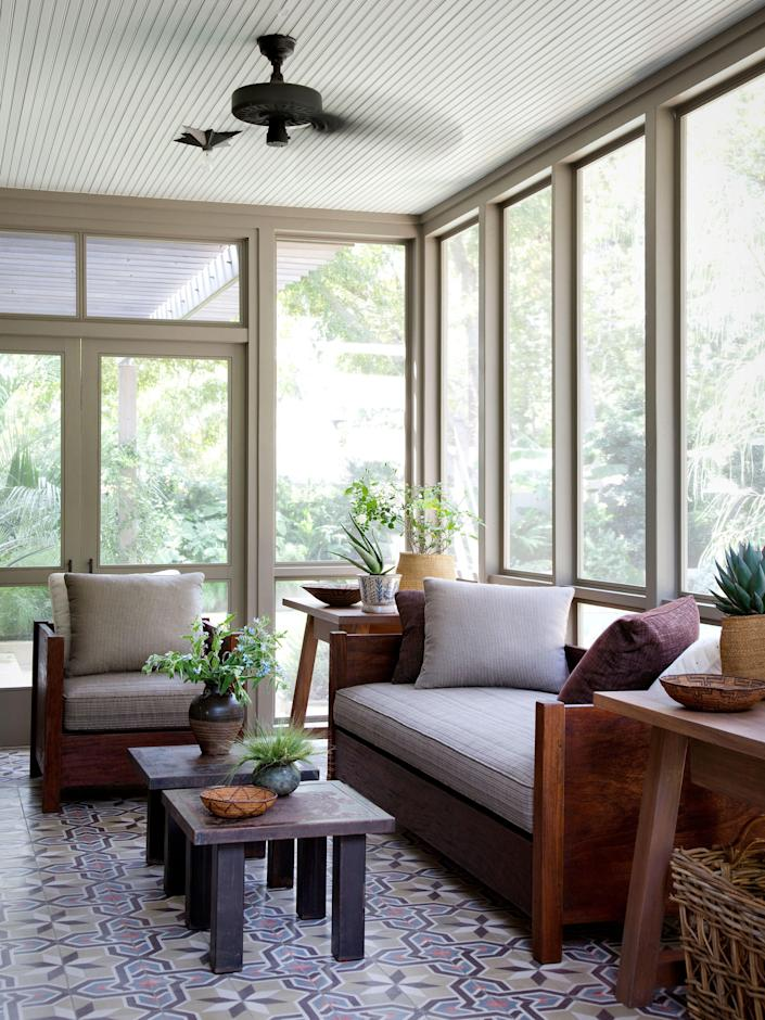 Moroccan cement tiles line the floor of the screened porch. Steel tables by Blend Interiors.