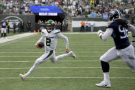 New York Jets quarterback Zach Wilson (2) runs the ball against Tennessee Titans defensive end Denico Autry (96) during overtime of an NFL football game, Sunday, Oct. 3, 2021, in East Rutherford, N.J. (AP Photo/Bill Kostroun)