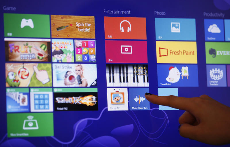 An attendant demonstrates the Microsoft Windows 8 operating system during its launching ceremony in Hong Kong Friday, Oct. 26, 2012. Microsoft launched a radical redesign of its world-dominating Windows operating system, introducing a touch-enabled interface that attempts to bridge the gap between personal computers and fast-growing mobile devices powered by the company's fiercest competitors. (AP Photo/Kin Cheung)