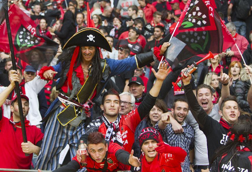 Supporters of French rugby team Toulon wave flags upon the arrival of Toulouse players during their Top 14 final rugby match at Stade de France stadium in Saint Denis, north of Paris, France, Saturday, June 1 2013. (AP Photo/Jacques Brinon)