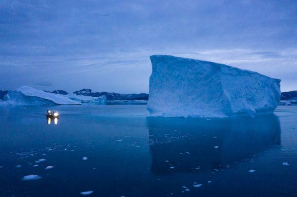 PHOTO: In this Aug. 15, 2019, photo, a boat navigates at night next to large icebergs in eastern Greenland. Greenland's ice has been melting for more than 20 years. (Felipe Dana/AP)