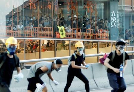 FILE PHOTO: People inside a restaurant watch as protesters attend a demonstration in support of the city-wide strike and to call for democratic reforms outside Central Government Complex in Hong Kong