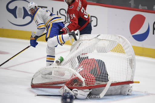 The net falls onto Washington Capitals goaltender Vitek Vanecek (41) during the first period of an NHL hockey game as Buffalo Sabres right wing Kyle Okposo (21) looks on Sunday, Jan. 24, 2021, in Washington. (AP Photo/Nick Wass)