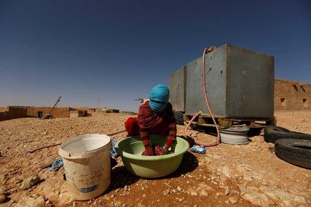 An indigenous Sahrawi woman washes her laundry in a refugee camp of Boudjdour in Tindouf