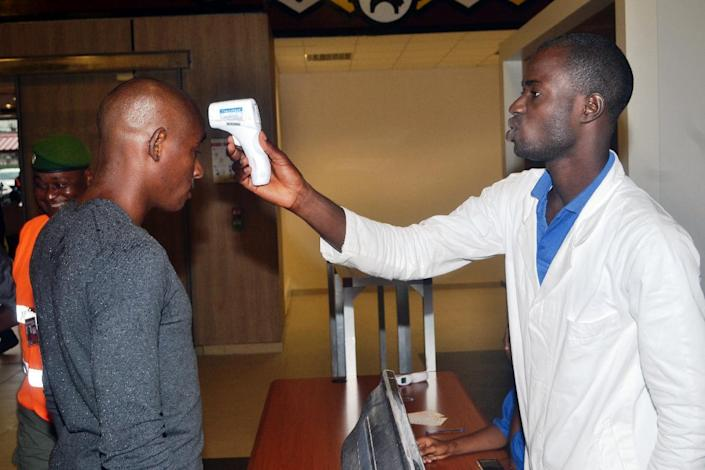 A health agent checks a passenger leaving the country at Conakry's airport on July 22, 2014 (AFP Photo/Cellou Binani)