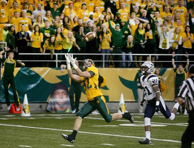 North Dakota State receiver Zach Vraa (82) hauls in a long touchdown pass from quarterback Brock Jensen ahead of New Hampshire defender Steven Thames (21) during the first half of an NCAA college semifinal football playoff game, Friday, Dec. 20, 2013, at the Fargodome in Fargo, N.D. (AP Photo/Bruce Crummy)