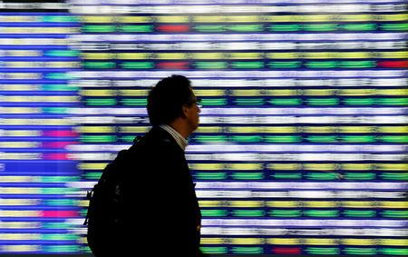 A man walks past an electronic stock quotation board outside a brokerage in Tokyo, Japan, November 13, 2018.   REUTERS/Toru Hanai