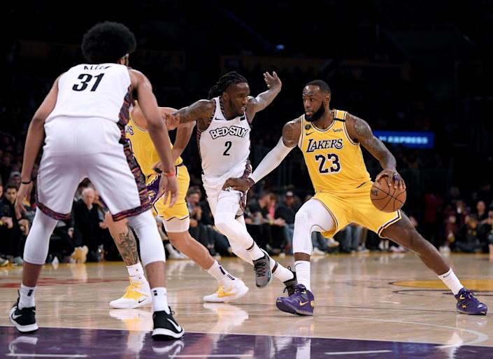 "Lakers forward LeBron James drives against the Nets on March 10 during both team's final game before suspension of play in the NBA. <span class=""copyright"">(Harry How / Getty Images)</span>"