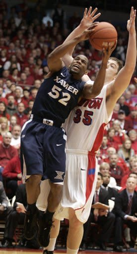 Xavier's Tu Holloway (52) grabs a rebound from Dayton's Matt Kavanaugh (35) during the first half of an NCAA college basketball game played, Saturday, Jan. 21, 2012, in Dayton, Ohio. (AP Photo/Skip Peterson)