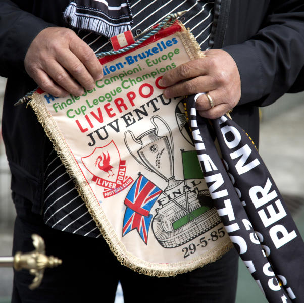 FILE - In this May 29, 2015 file photo, Italy's Domenico Di Bernardo holds an original banner from the 1985 match during a commemoration at the King Boudouin (formerly the Heysel) Stadium in Brussels. Friday, May 29, 2020 marks 35 years since 39 victims lost their lives during a European Cup football match between Liverpool and Juventus due to a surge of rival supporters resulting in a collapsed wall. (AP Photo/Virginia Mayo, File)