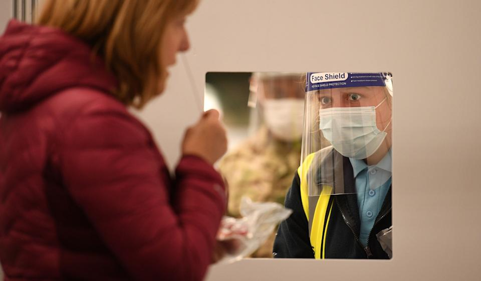 A member of the public uses a swab before passing it to a waiting member of Test and Trace at the mass and rapid testing centre for the novel coronavirus COVID-19 at a Tennis centre in Liverpool on November 6, 2020. - To avoid extending the lockdown, Johnson is pinning his hopes on an ambitious new programme of Covid testing to detect and isolate infected people, starting with a city-wide trial launching in Liverpool today. (Photo by Oli SCARFF / AFP) (Photo by OLI SCARFF/AFP via Getty Images)