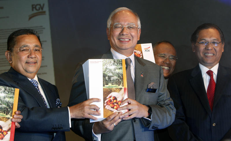 Malaysian Prime Minister Najib Razak, center, holds Felda Global Ventures Holdings' newly launched prospectus as he poses with Felda Chairman Mohd Isa Samad, left, and Felda Chief Executive Sabri Ahmad, right, in Kuala Lumpur, Malaysia, Thursday, May 31, 2012. Malaysian plantation giant Felda Global Venture Holdings says its initial public offering this month could raise as much as 10.5 billion ringgit ($3.3 billion), the second biggest after Facebook. (AP Photo/Lai Seng Sin)
