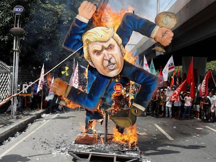 Trump in Philippines: President hails 'red carpet like nobody has ever received' while Manila protesters burn effigy of him