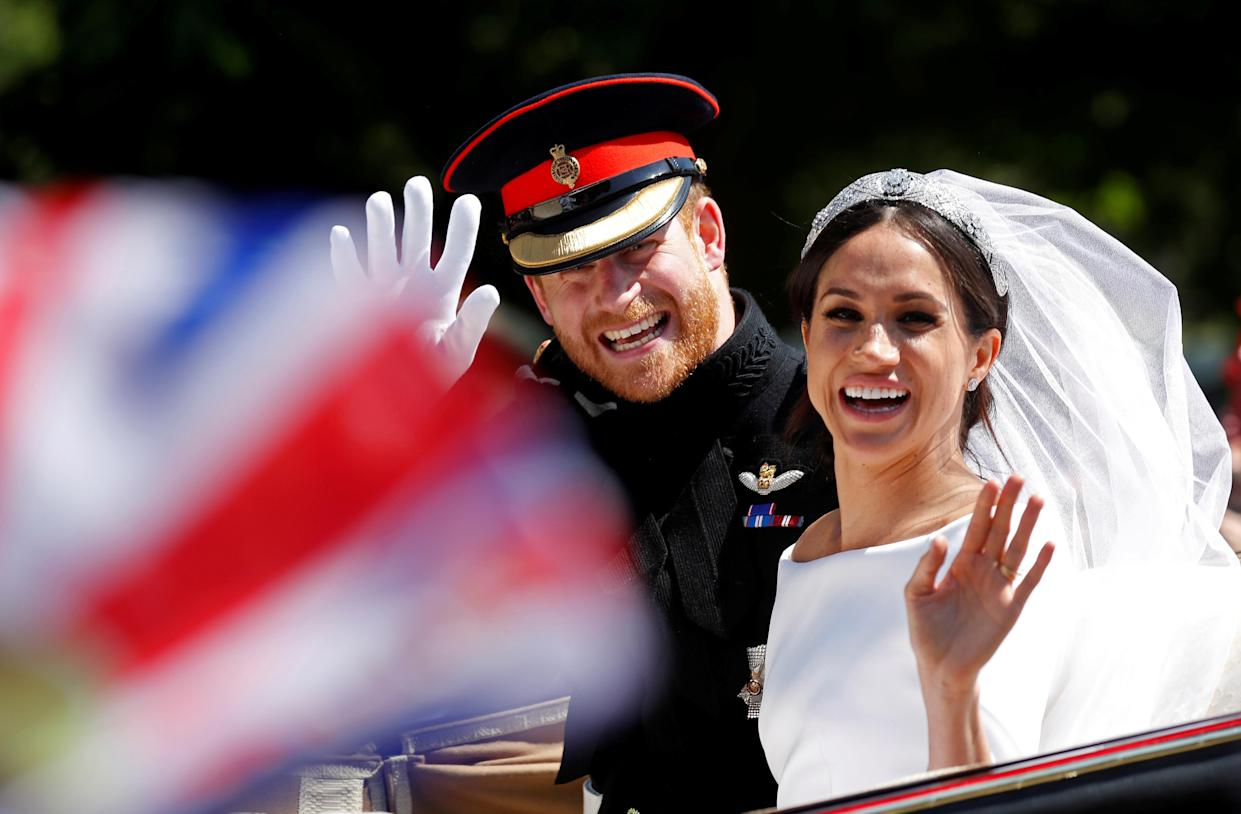 Britain's Prince Harry and his wife Meghan wave as they ride a horse-drawn carriage after their wedding ceremony at St George's Chapel in Windsor Castle in Windsor, Britain, May 19, 2018. REUTERS/Damir Sagolj     TPX IMAGES OF THE DAY