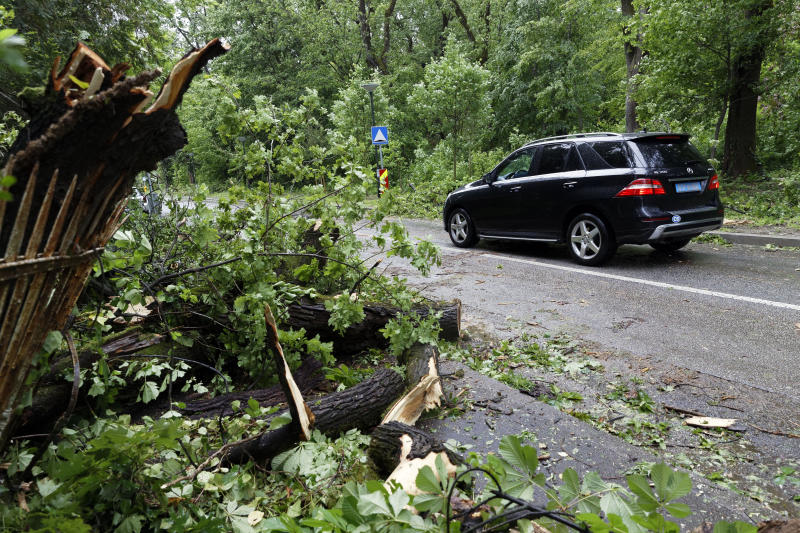 A car drives past fallen branches of a tree, in Zagreb, Croatia, Monday May 13, 2019. Stormy winds have uprooted trees, knocked over traffic lights and disrupted traffic in Croatia, injuring two people and prompting authorities on Monday to advise people to stay indoors. (AP Photo/Darko Bandic)
