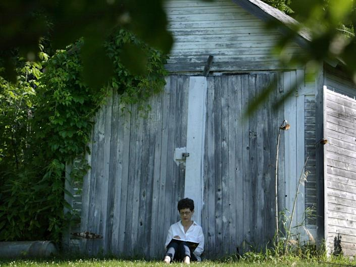 A woman sits in front of a barn in Stockholm, Wisconsin.