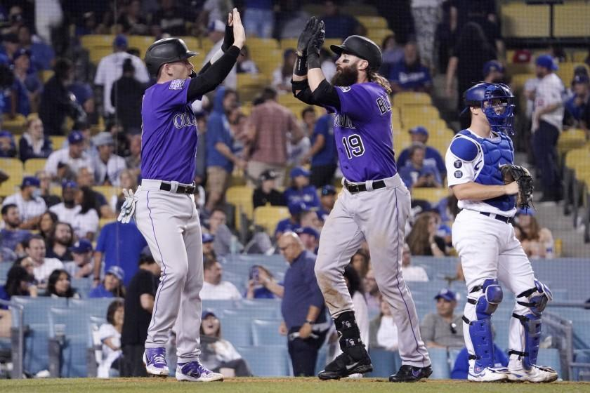 The Rockies' Charlie Blackmon, center, celebrates with Trevor Story after Blackmon hit a two-run homer in the 10th inning.