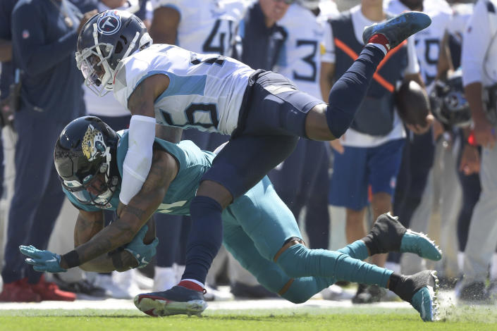 Jacksonville Jaguars wide receiver Marvin Jones, left, is brought down after a reception by Tennessee Titans cornerback Kristian Fulton during the first half of an NFL football game, Sunday, Oct. 10, 2021, in Jacksonville, Fla. (AP Photo/Phelan M. Ebenhack)