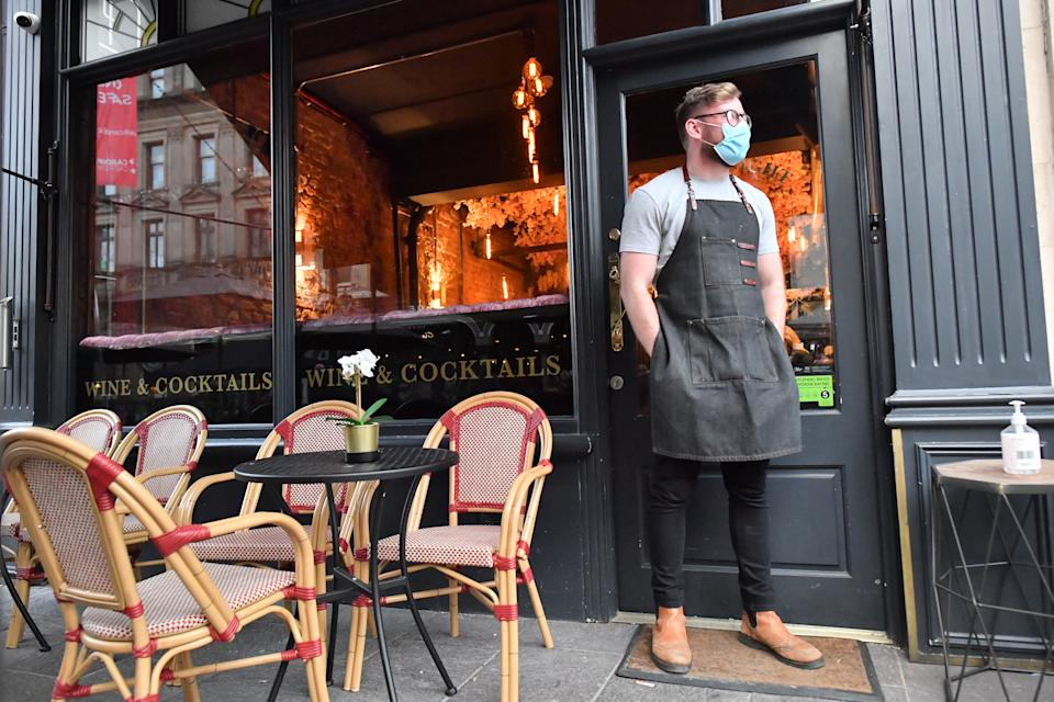 A bartender wearing a face mask stands outside a bar in Cardiff ahead of pubs, bars, restaurants and cafes shutting at 6pm and no longer being able to serve alcohol as part of a new round of coronavirus restrictions that come into force in Wales on Friday night. (Photo by Ben Birchall/PA Images via Getty Images)