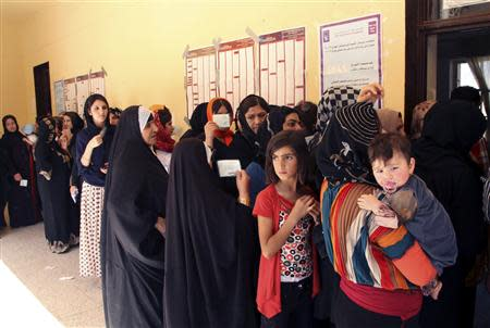 Iraqi Kurds line up at a polling station before voting during the regional parliamentary elections at a polling station in Arbil