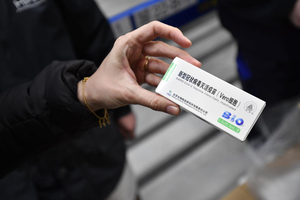 A woman holds a packet containing vials of the COVID-19 vaccine developed by the Chinese state-owned company Sinopharm at a Hungarian pharmaceutical wholesaler in Budapest, Hungary, Tuesday, Feb. 16, 2021. A shipment of COVID-19 vaccines produced in China arrived in Hungary on Tuesday, making it the first of the European Union's 27 nations to receive a Chinese vaccine. (Marton Monus/MTI via AP)