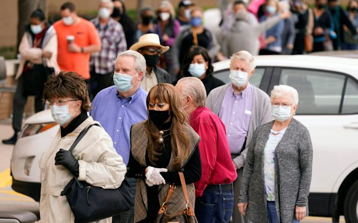People wait in line to receive a COVID-19 vaccination at Methodist Hospital in the Oak Cliff section of Dallas. Texas - AP