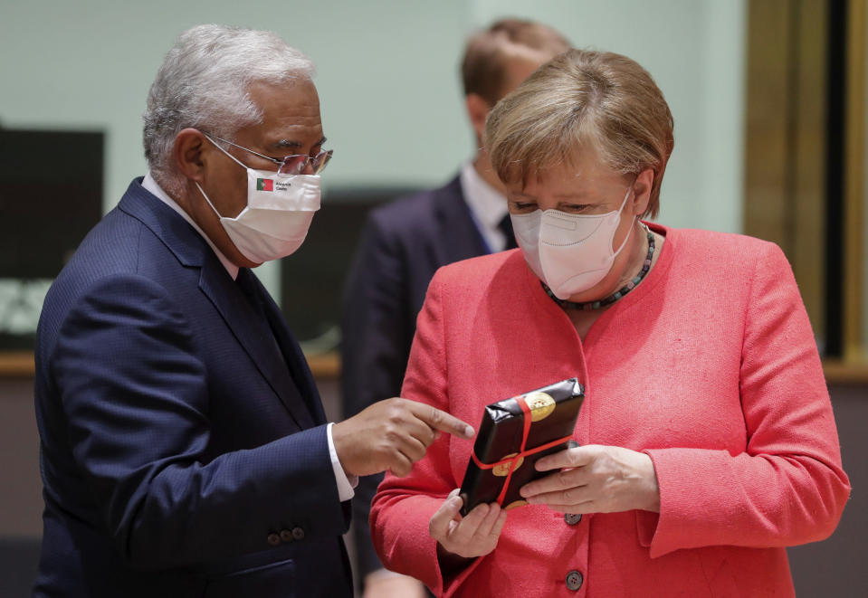 German Chancellor Angela Merkel, right, receives a gift from Portugal's Prime Minister Antonio Costa during a round table meeting at an EU summit in Brussels, Friday, July 17, 2020. Leaders from 27 European Union nations meet face-to-face on Friday for the first time since February, despite the dangers of the coronavirus pandemic, to assess an overall budget and recovery package spread over seven years estimated at some 1.75 trillion to 1.85 trillion euros. (Stephanie Lecocq, Pool Photo via AP)