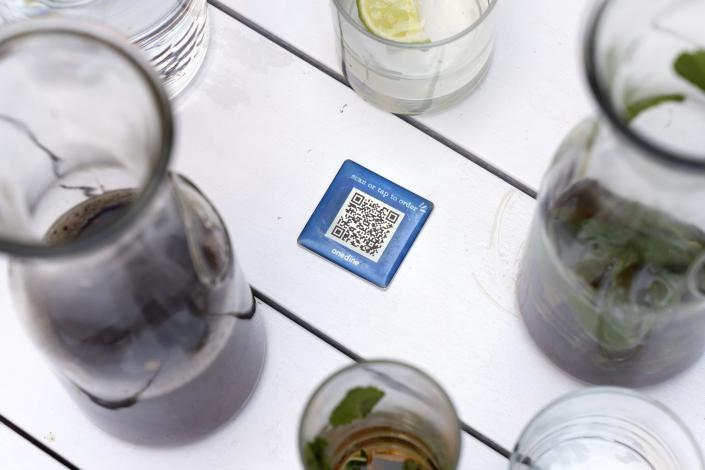 """Drinks surround a barcode attached to the table at Bartaco, that patrons use to order and pay at the restaurant in Arlington, Va., on Thursday, Sept. 2, 2021. The restaurant uses an automated app for ordering and payments. Instead of servers Bartaco uses """"food runners"""" to bring the orders to the tables. (AP Photo/Jacquelyn Martin)"""