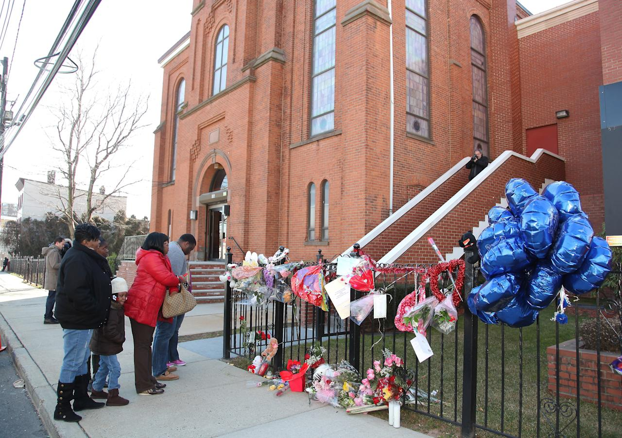 """NEWARK, NJ - FEBRUARY 13:  People view a makeshift memorial outside """"The New Hope Baptist Church"""" on February 13, 2012 in Newark, New Jersey. Singer Whitney Houston died on February 11, 2012 at The Beverly Hilton hotel in Beverly Hills, California.  (Photo by Paul Zimmerman/Getty Images)"""